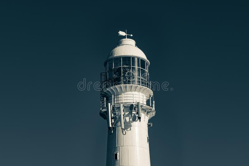 Black and white close up of a lighthouse against the sky. A black and white, lighthouse againstthe sky in Kommetjie, Cape Town, South Africa royalty free stock photography