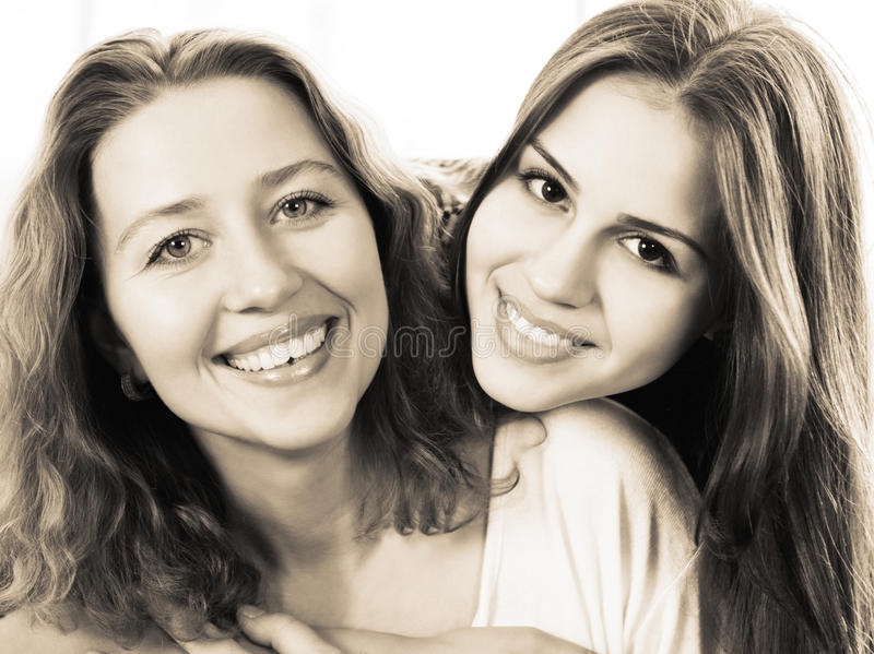 Black and white close up portrait of a mother and teen daughter. Being close and hugging at home being happy and joyful royalty free stock photography