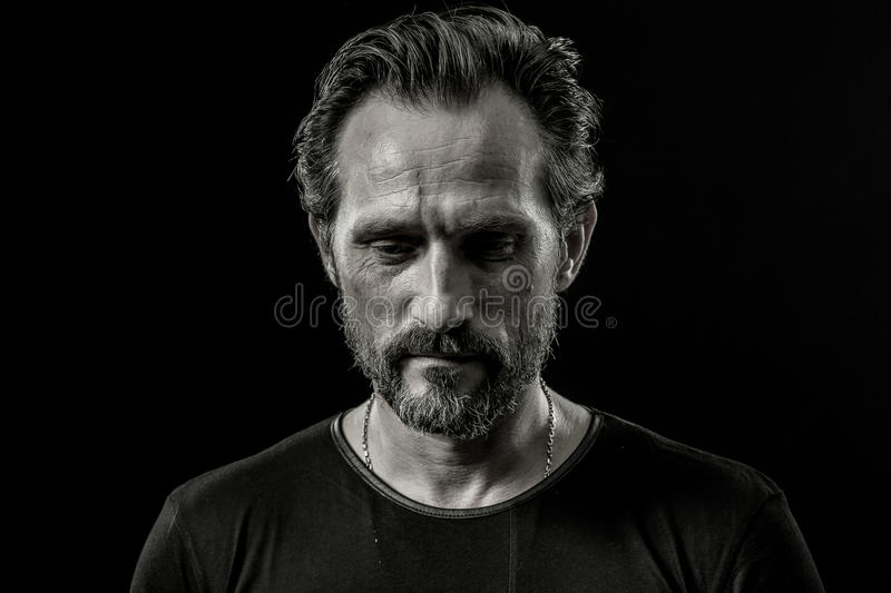 Black and white close up portrait of a severe man with sad facial expression. stock image