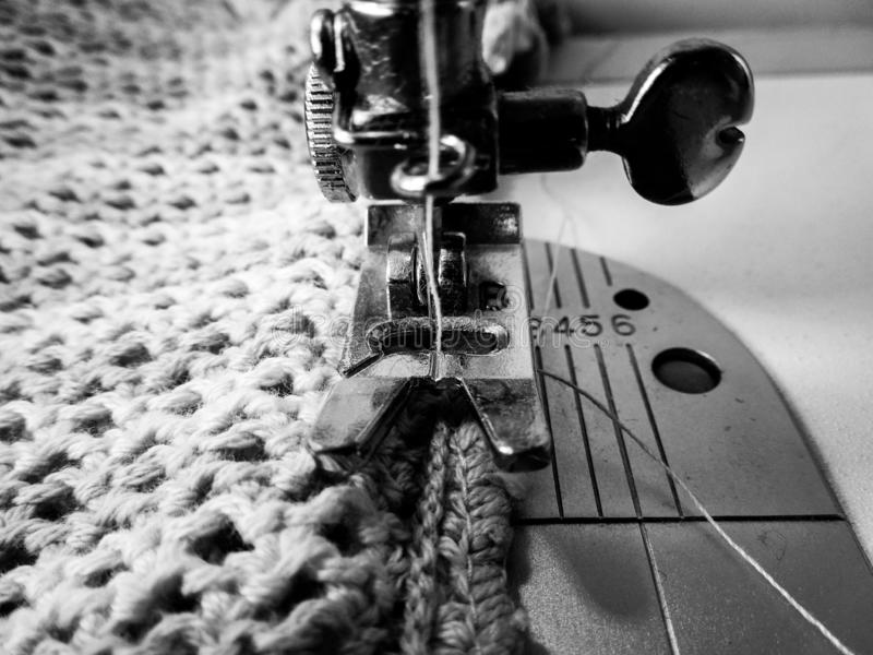 Needle of a sewing machine sewing a crocheted fabric royalty free stock images