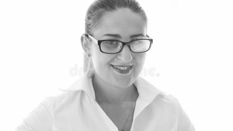 Black and white closeup portrait of smiling young woman in eyeglasses looking in camera stock images