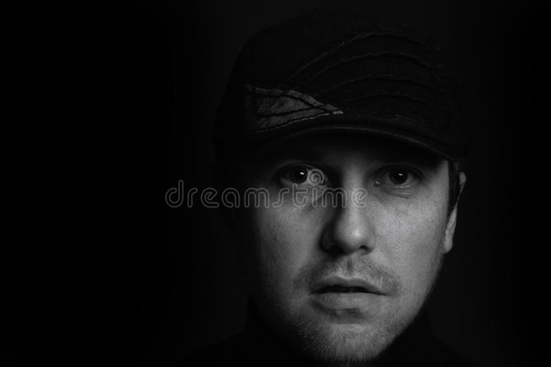 Black and white closeup portrait of an unshaven serious young gangster man with a cap on a dark background royalty free stock photo