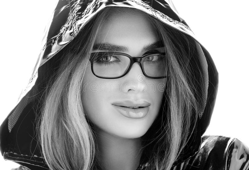 Black and white closeup portrait of young beautiful woman in glasses and a hood royalty free stock images