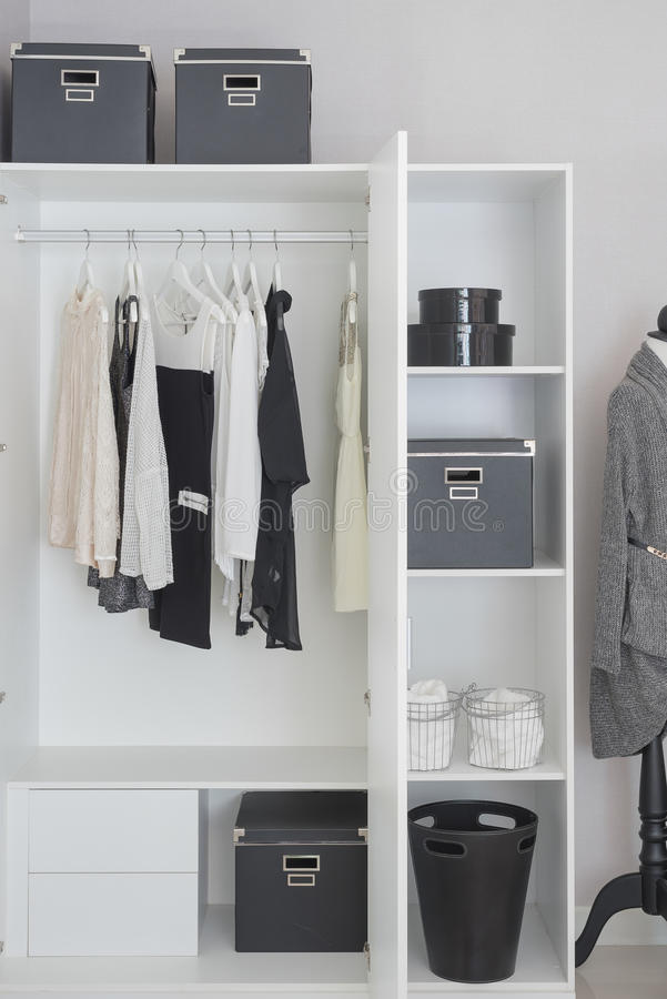Black and white clothes hanging in wardrobe. Black and white clothes hanging in white wardrobe royalty free stock images