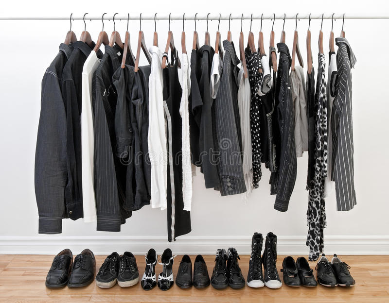 Black and white clothes for man and woman. Female and male black and white clothes on a rod and shoes on a wooden floor royalty free stock images