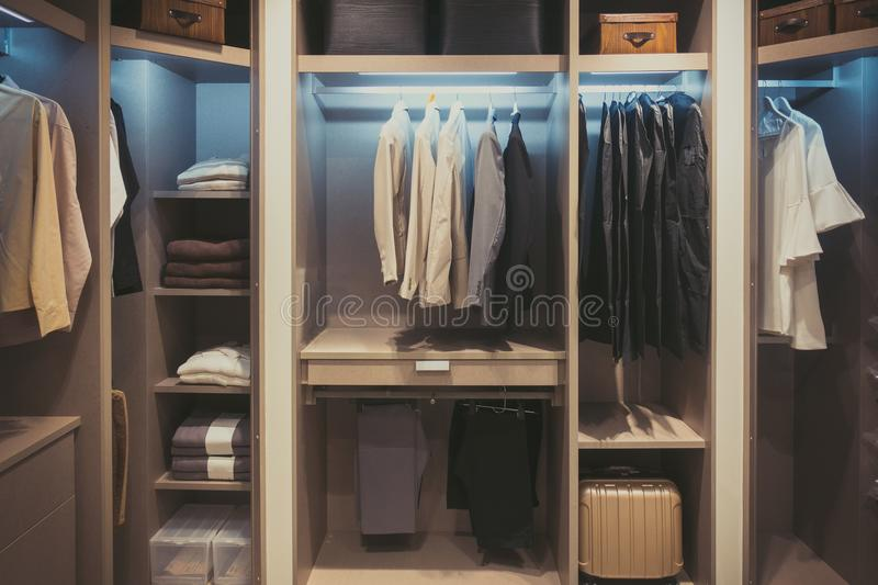 Black and white cloths hanging in wooden wardrobe at home.  stock photo
