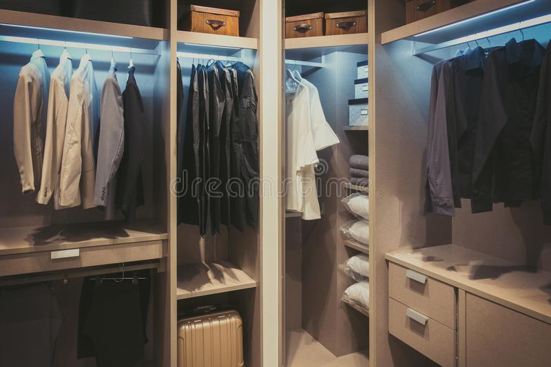 Black and white cloths hanging in wooden wardrobe at home.  stock photography