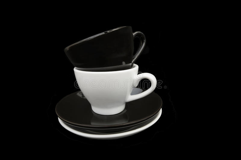 Black and White coffee cupsBlack and White coffee cups. Two stacked black and white coffee cups and saucers. Isolated on a black background stock images