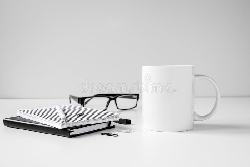 Black and white coffee mug mock up with notebooks, pen and eyeglasses royalty free stock images