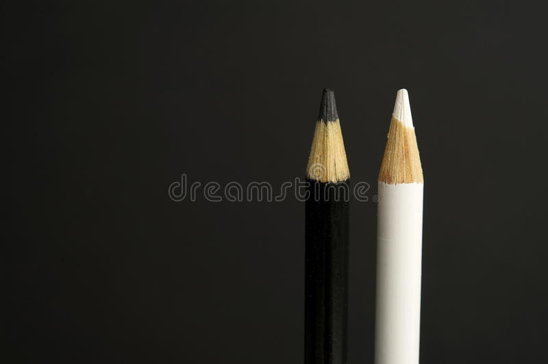 Black and white coloured pencil crayons on a black background royalty free stock photography