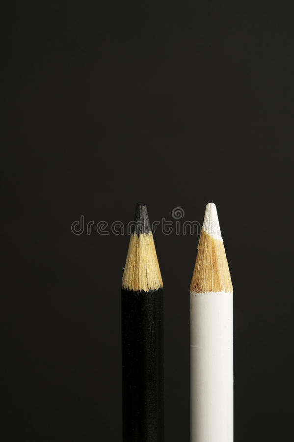 Black and white coloured pencil crayons on a black background royalty free stock photo