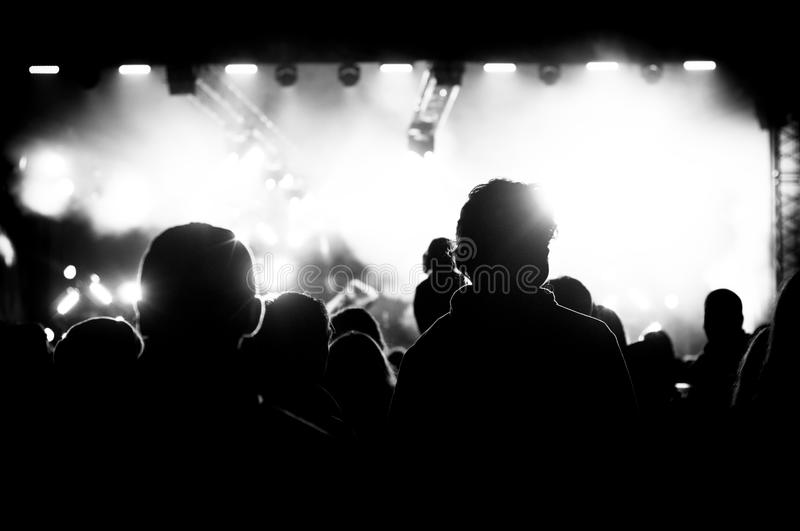 Black and white concert. Crowd next to the white concert lights royalty free stock images