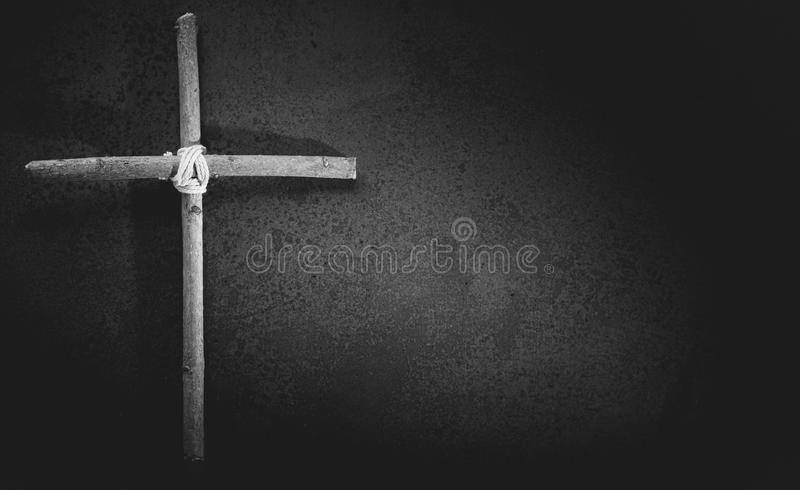 Black and white condolence card. With basic wooden crucifix or cross on heavy stone background royalty free stock images