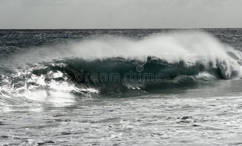 Black and White Crashing Waves. Black and white photograph of the dangerous shorebreak waves crashing on Sandy beach, on the South Shore of Oahu royalty free stock image