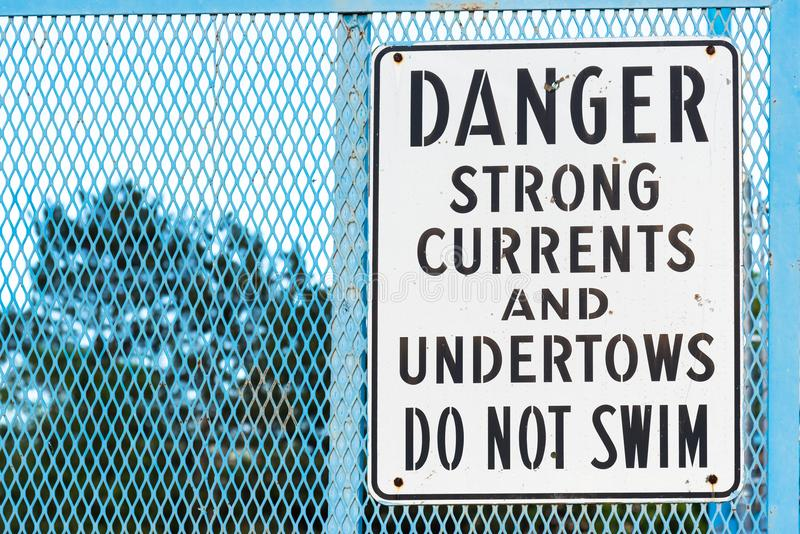 Sign by river warning of strong currents and undertows no swimming. Black and white danger sign on blue fence warning of strong currents and undertows royalty free stock image
