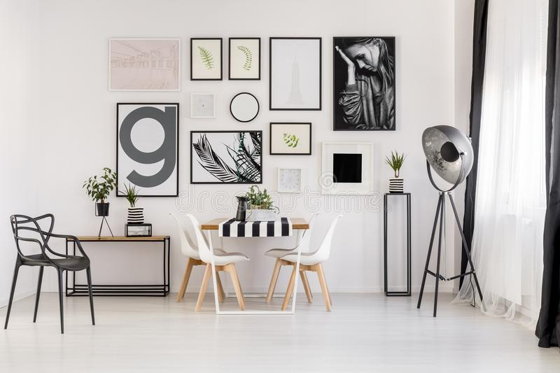 Black and white dining room. Lamp near white chairs at wooden table in dining room interior with posters and black armchair stock photography