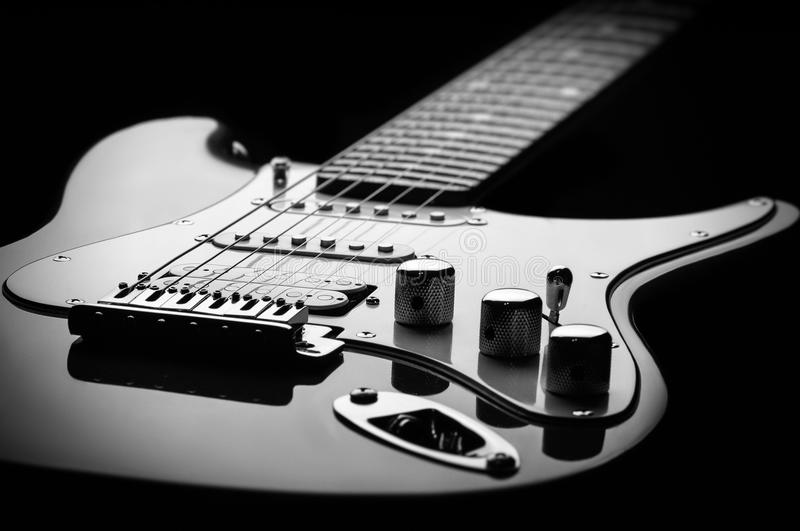 Black and white electric guitar on a black background stock photo