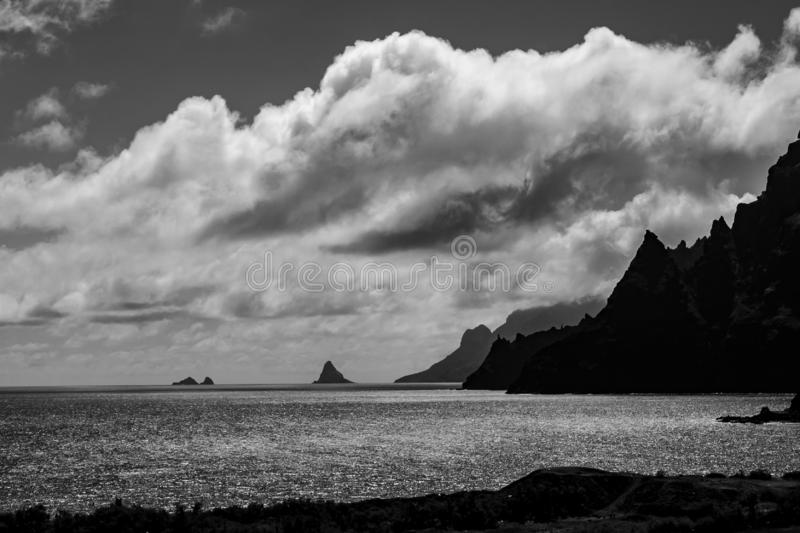 Black and white far view over the sea with rocks royalty free stock photography