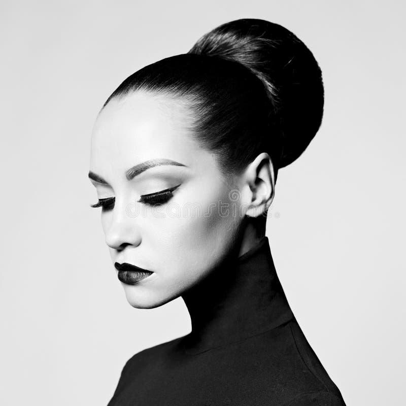 Beautiful elegant woman in black turtleneck. Black and white fashion art studio portrait of beautiful elegant woman in black turtleneck. Hair is collected in stock photo