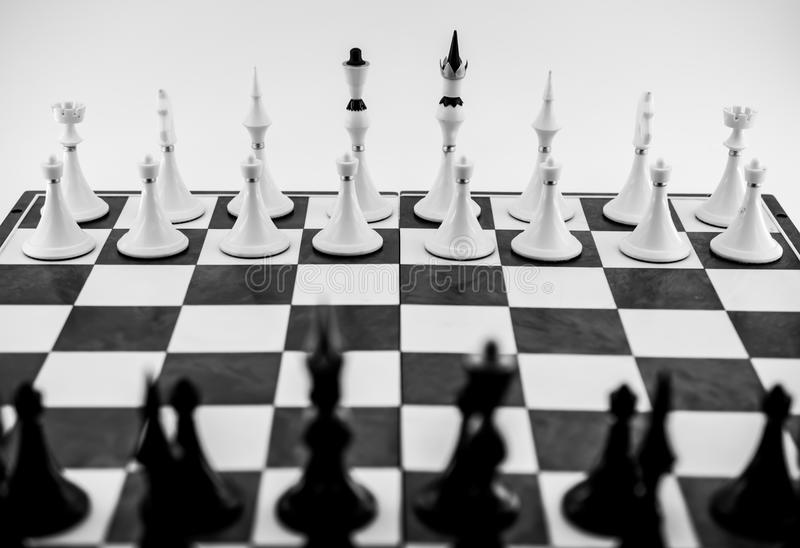 Black and white figures on a chessboard. Suitable for symbolic meaning in business, expression of strategy, desire for victory, defeat or gain royalty free stock images