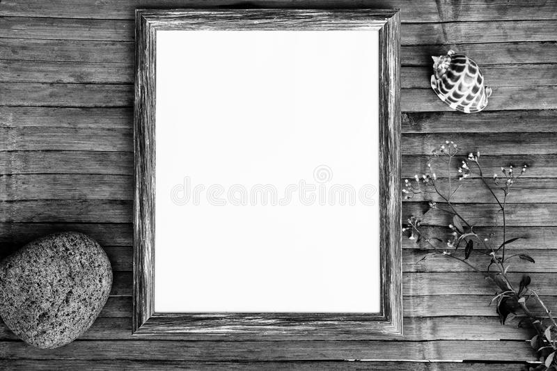 Black and white flat lay with sea pebble and shell. Shabby chic banner template with place for text. Blank page in vertical wooden frame. Monochrome photo stock images