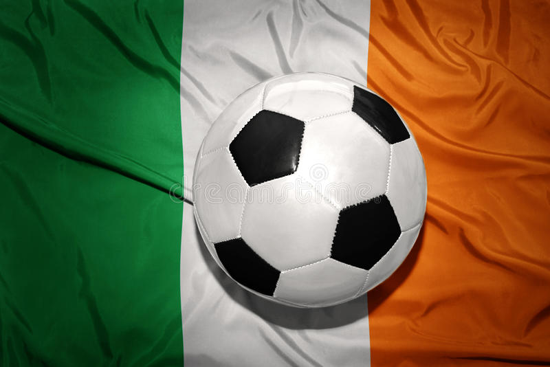 Black and white football ball on the national flag of ireland royalty free stock image