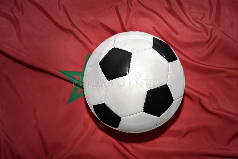 Black and white football ball on the national flag of morocco stock photography