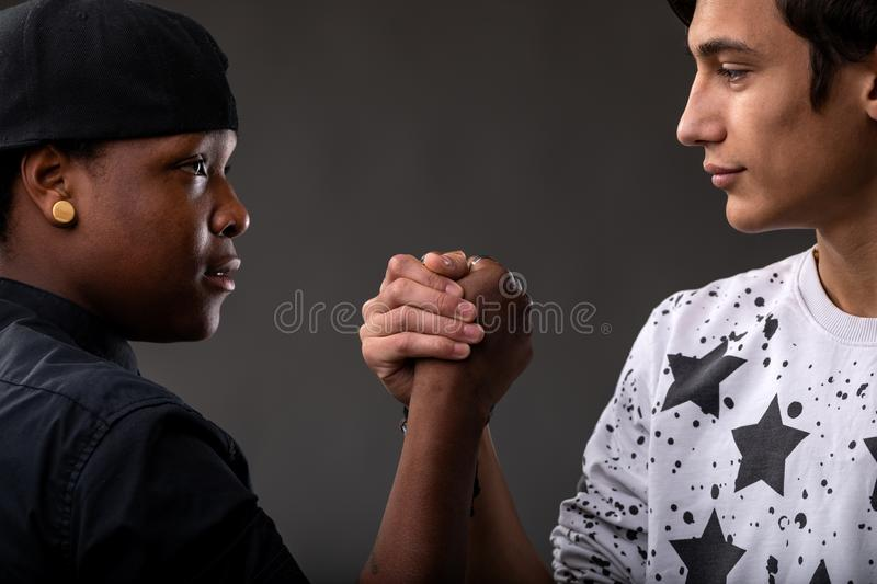 Black and white friends facing each other. And promising to tell the truth forever stock images