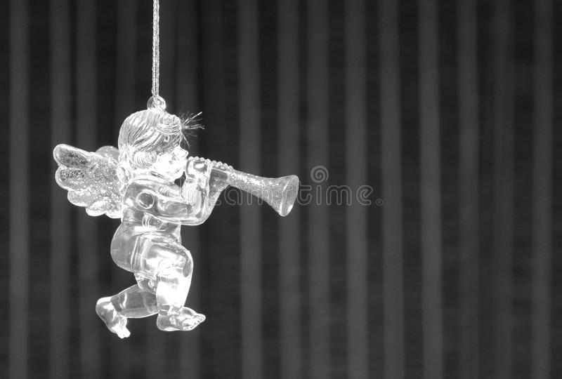 Black and white fur-tree toy in form of little angel`s figurine with wings and pipe on black-and-white background for Christmas stock image