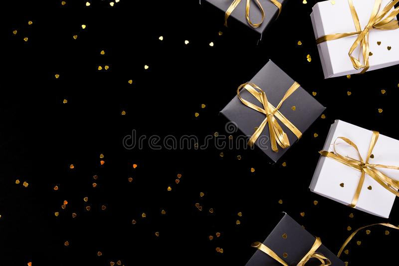 Black and white gift boxes with gold ribbon on shine background. Flat lay. Copy space. royalty free stock image
