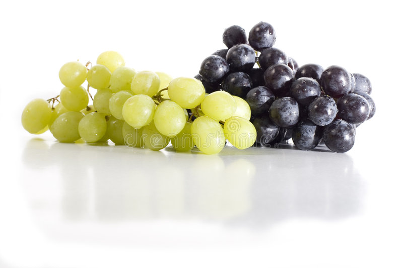 Black and White Grapes. Isolated black and white grapes reflecting on white glossy surface stock image