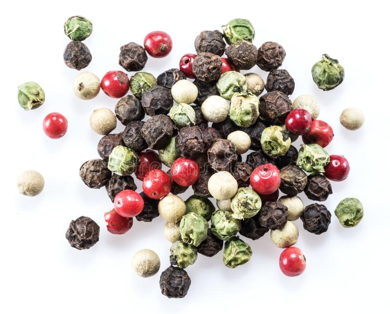 Black, white, green and red peppercorns isolated on white background.  stock images