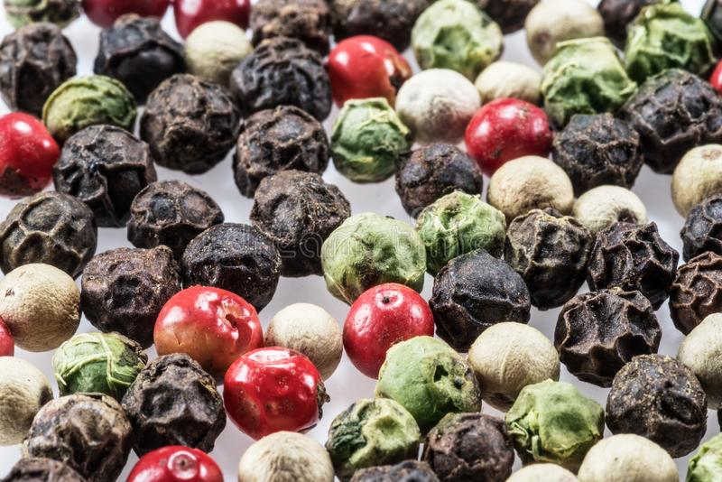 Black, white, green and red peppercorns isolated on white background.  royalty free stock images