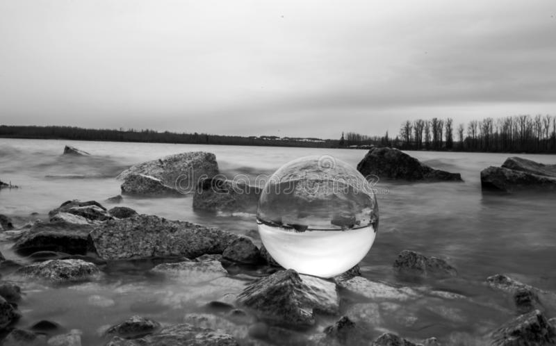 Black and White River Rocks with Clear Globe. Black and white grey tone of river and rocks with a clear globe resting stock images