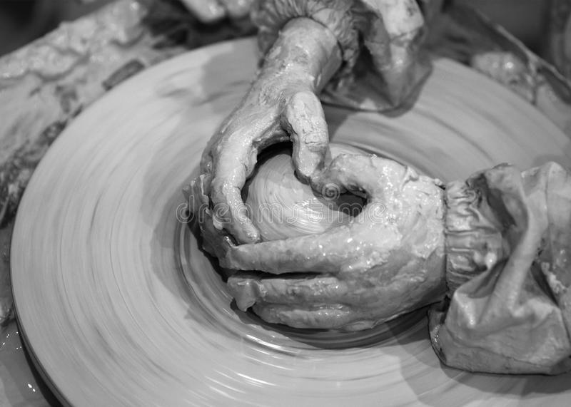Black and white hands of young girl in process of making clay bo stock image