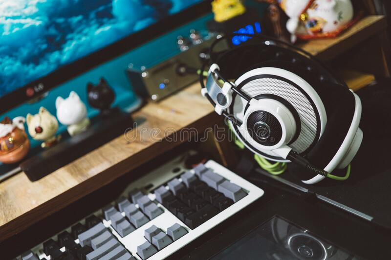 Black and White Headset Next to White Black and Gray Computer Keyboard royalty free stock photo