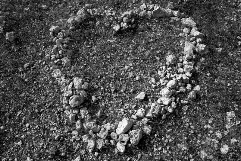 Black and white heart shape stones on soil. Romantic and dramatic royalty free stock photography