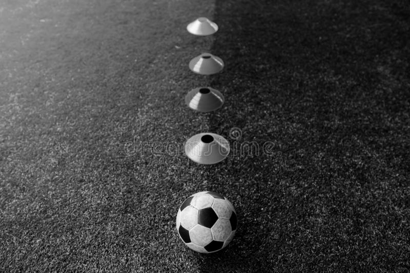 Black and white iamge of cone marker and football are soccer training equipment stock image