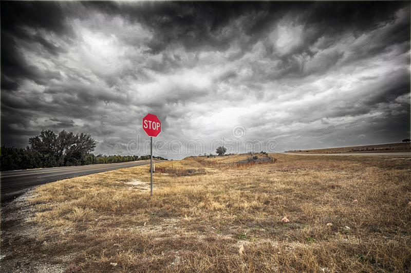 Stop Sign in the middle of nowhere. A black and white image with added color of a stop sign on a stormy day royalty free stock photos