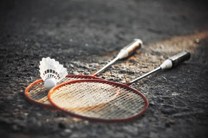 Shuttlecock and two bright red racquets for badminton. Black and white image of the asphalt, which put shuttlecock and two bright red racquets for badminton stock photo