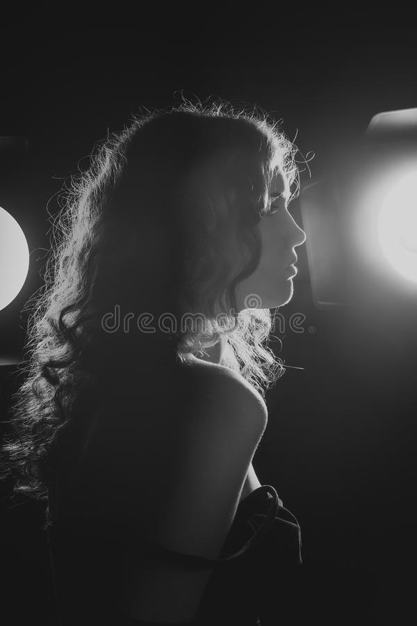 A black and white image of a beautiful young woman. Film noir style. Filtered stock photos