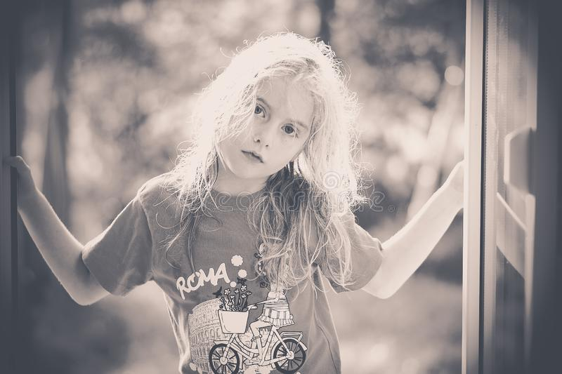 Black and white image of a blond little girl looking at me. Blue eyed blond little girl with sunny hair looking at me black and white processed image stock image