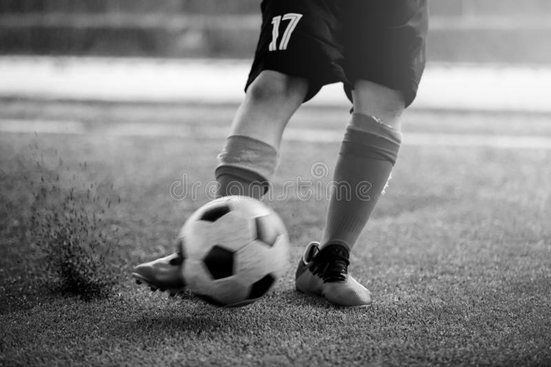 Black and white image of blurry ball after boy soccer player speed run on artificial turf to shoot it to goal. kid soccer player stock photography
