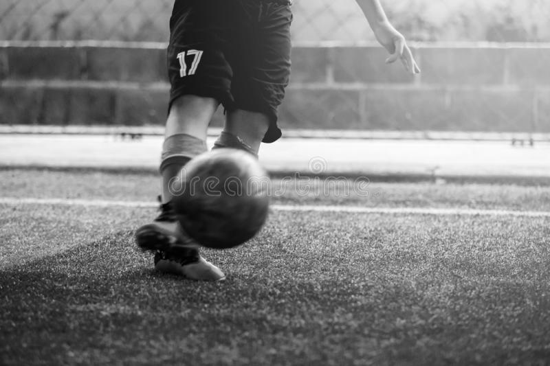 Black and white image of blurry ball after boy soccer player speed run on artificial turf to shoot it to goal. kid soccer player stock photo