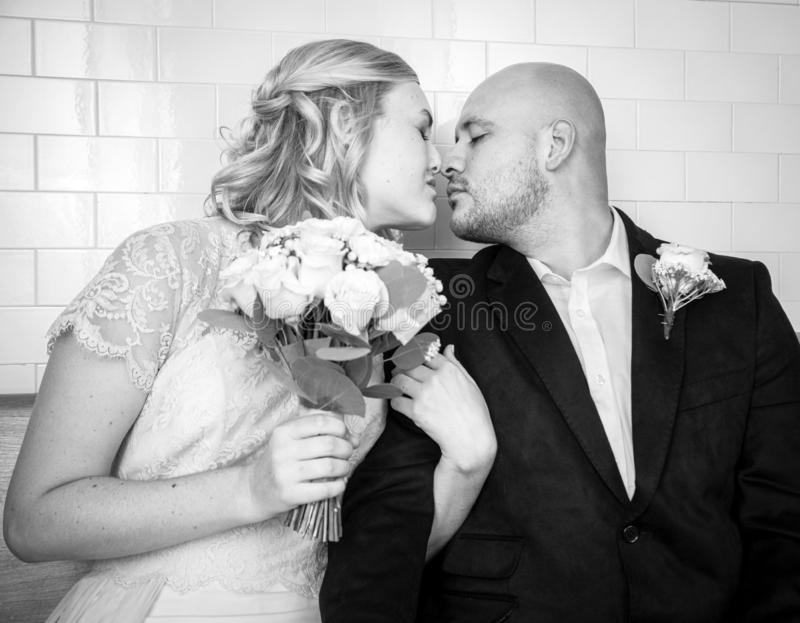 Black and White image of of bride and groom in vintage clothing sitting and kissing stock photo