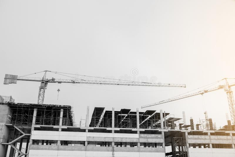 Black and white image of building crane and buildings under construction royalty free stock photo