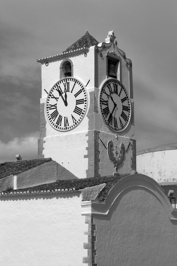 Clock tower of the Church of Santa Maria do Castelo, Tavira, Portugal. Black and white image of the clock tower of the Church of Santa Maria do Castelo, Tavira stock photo