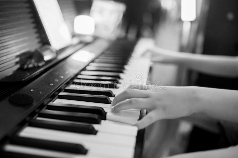 Black and white image of closeup kid`s hand playing piano on stage stock photos
