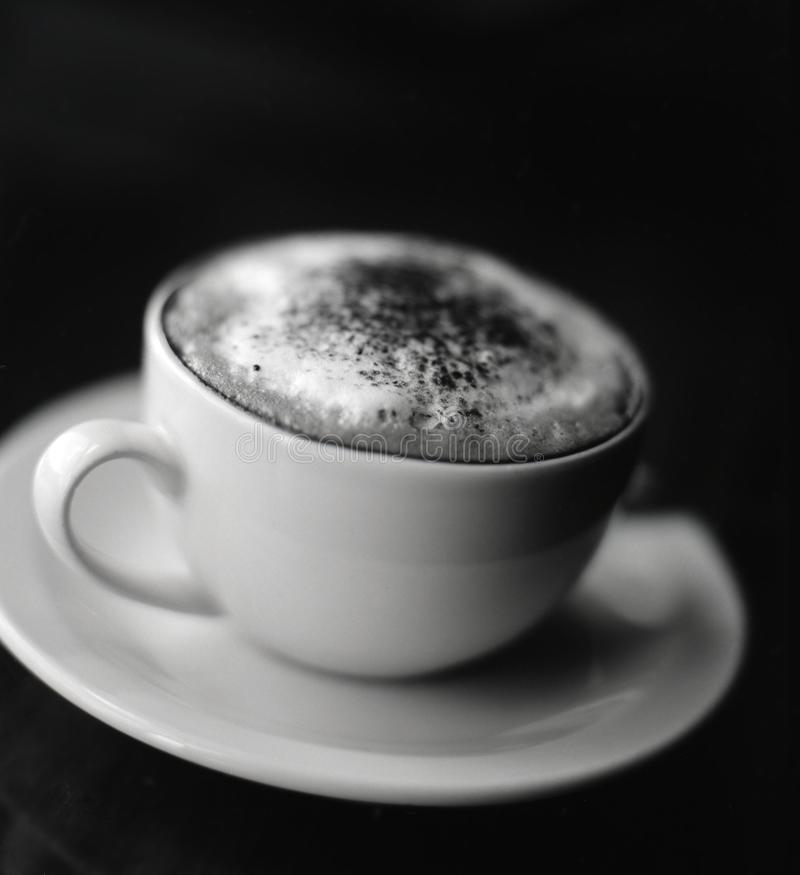 Black and white image of cup of cappuccino stock images