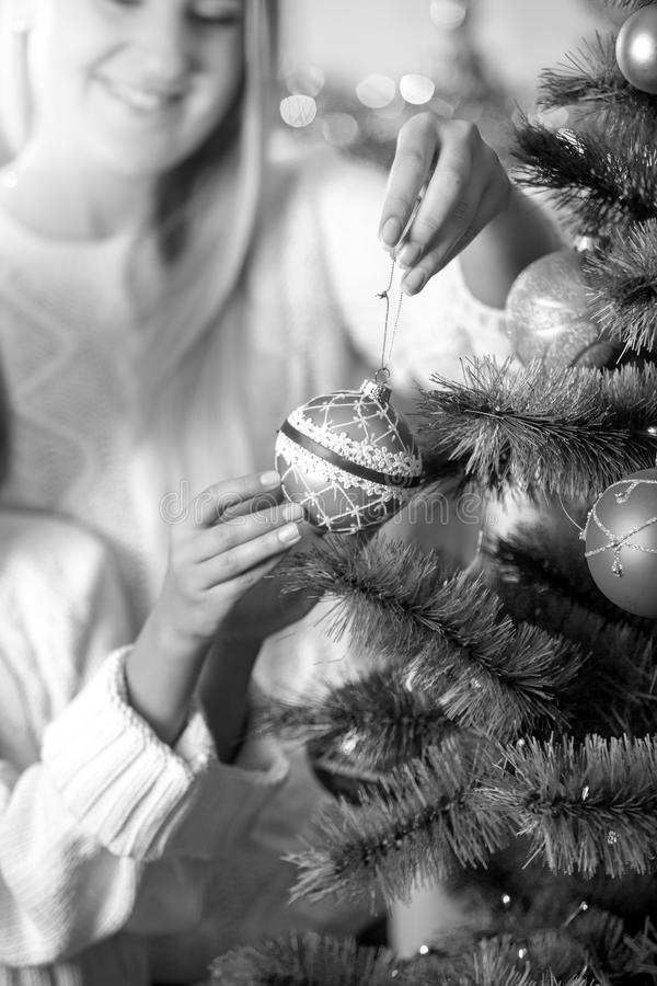 Black and white image of daughter helping mother in decorating C stock photo
